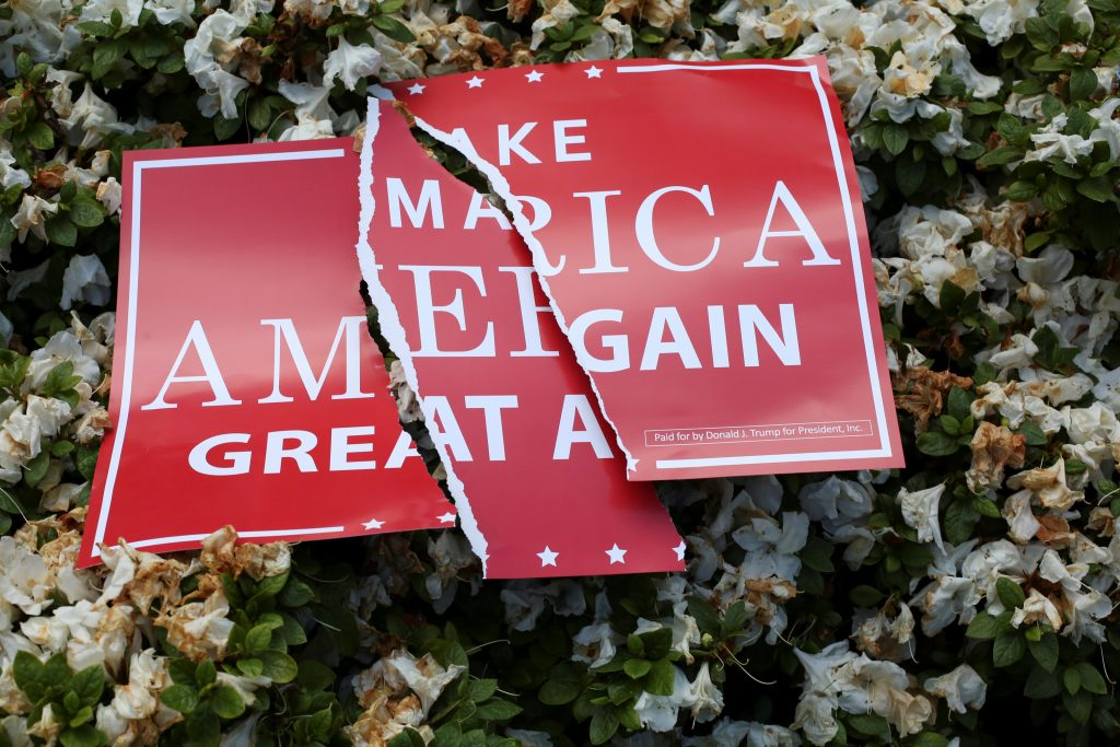 A torn sign rests on a bush during the Trump Free Speech Rally in P…