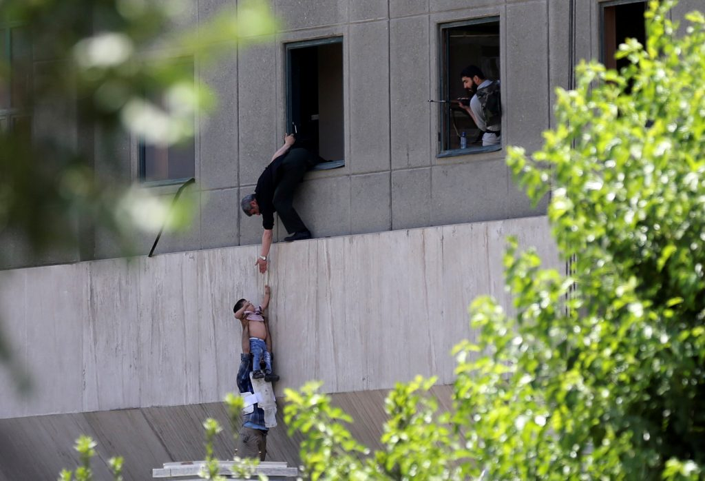 A boy is evacuated during an attack on the Iranian parliament in central Tehran on June 7. Photo by Omid Vahabzadeh/TIMA v...