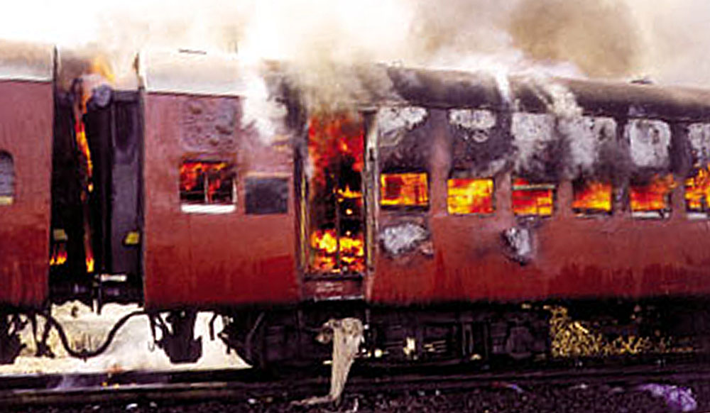 Smoke pours from the carriage of a train on fire in Godhra, in the western Indian state of Gujarat, February 27, 2002. Up to 56 people died on Wednesday after a train carrying Hindu activists from the controversial site of a razed mosque was set on fire in western India, officials said. ? QUALITY AVAILABLE REUTERS - RTXL3IW