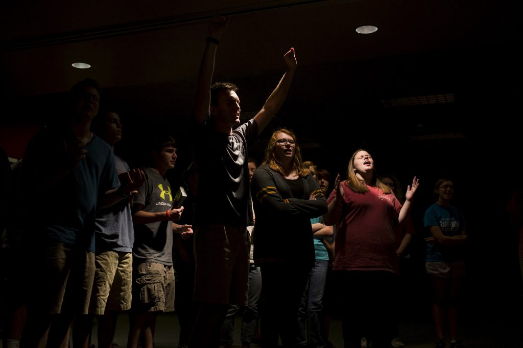 Geyna Moore, 19, raises up her hands amongst other students during a worship service at the Baptist Campus Ministry at Western Kentucky University in Bowling Green, United States, September 23, 2015. In the Bible Belt of southern U.S. states, Kentucky and Georgia among them, church and religion are ever present, from well-attended services to prayer groups and choirs. Crosses hang from necklaces and prayers are said before meals and Little League baseball sessions. Even so, Americans as a whole are becoming less religious, judging by such markers as church attendance, prayer and belief in God, according to a recent poll by Pew Research Center. Picture taken September 23, 2015. REUTERS/Brittany Greeson - RTS66II