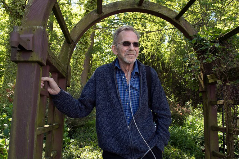 Bruce Mead-e, 63, who has advanced lung cancer, stands in the garden at his home in Georgetown, Del. Over four years, he has undergone two major surgeries, multiple rounds of radiation and chemotherapy. (Eileen Blass for Kaiser Health News)