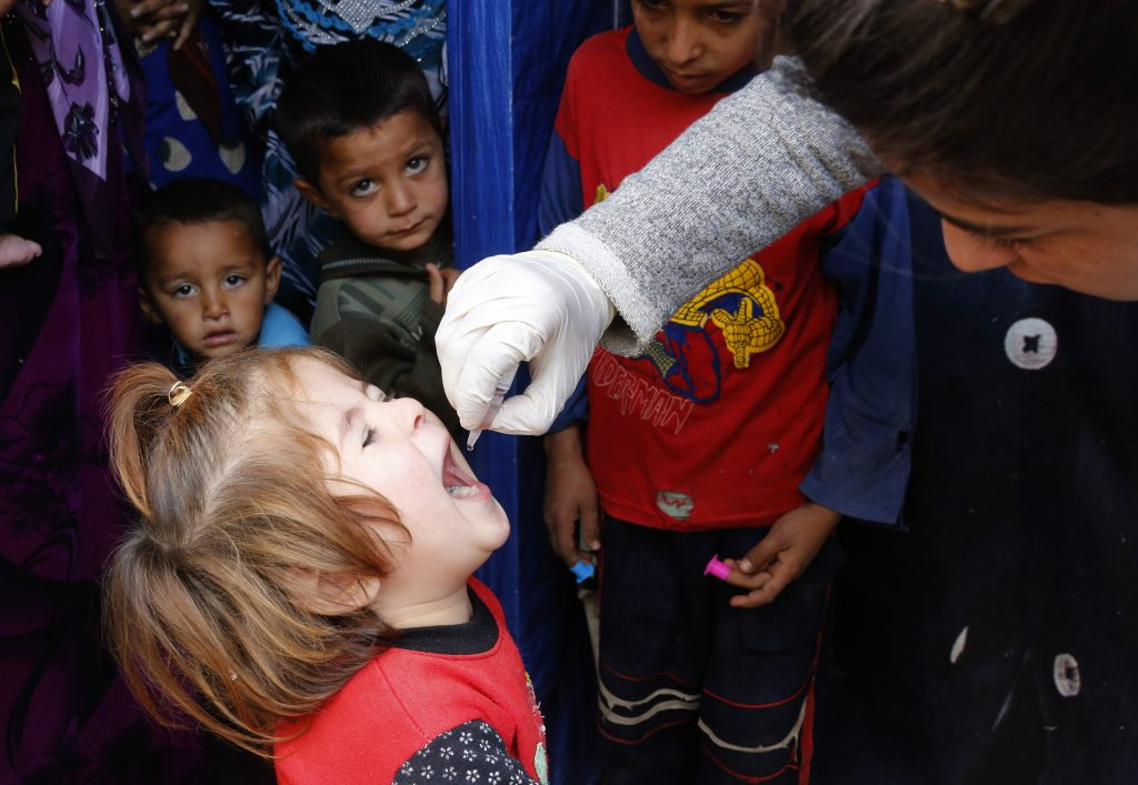 A child receives polio vaccination at an informal settlement of Syrian refugee in Zahle in the Bekaa valley October 16, 2014. Photo by Mohamed Azakir/REUTERS
