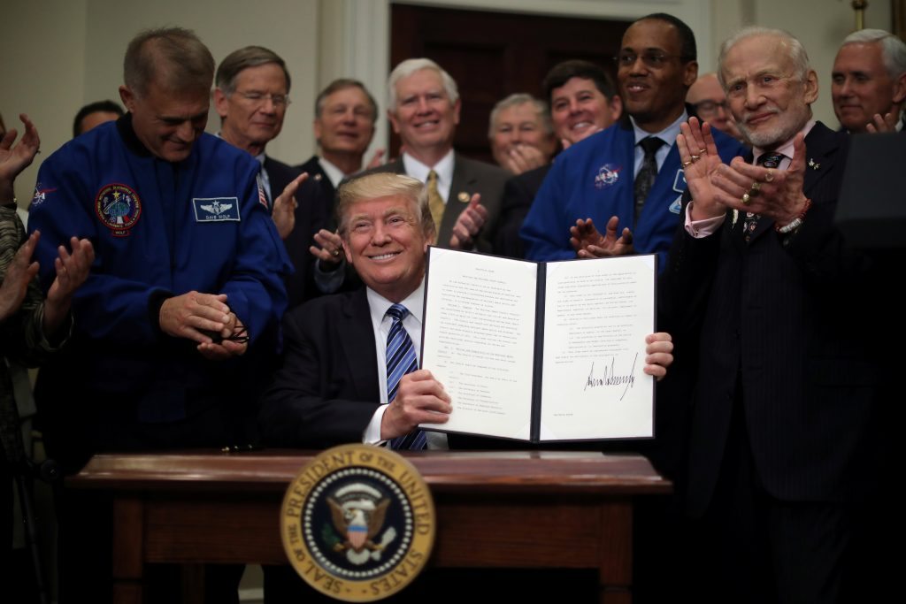 President Donald Trump signs an executive order to create the National Space Council, accompanied by former astronauts Buzz Aldrin (2nd-R), Alvin Drew (3rd-R) and Dave Wolf (L) in the Roosevelt room of the White House, in Washington, DC, U.S. June 30, 2017. REUTERS/Carlos Barria        TPX IMAGES OF THE DAY - RTS19BDI