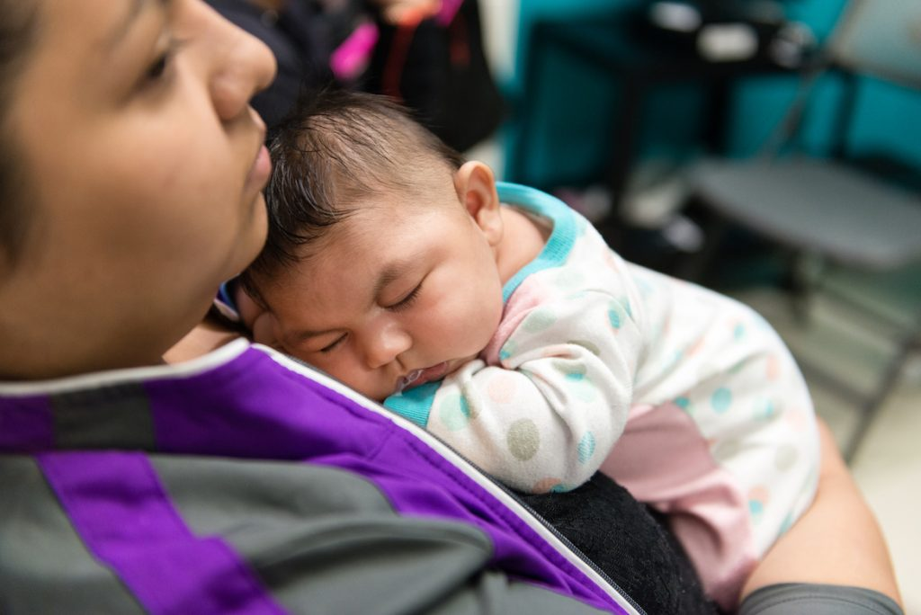 Jessica Rios holds niece Aryanna Guadalupe Sanchez-Rios as she naps between exams at Seattle Children's Hospital in Seattle, WA., on May 5, 2017. (Heidi de Marco/KHN)