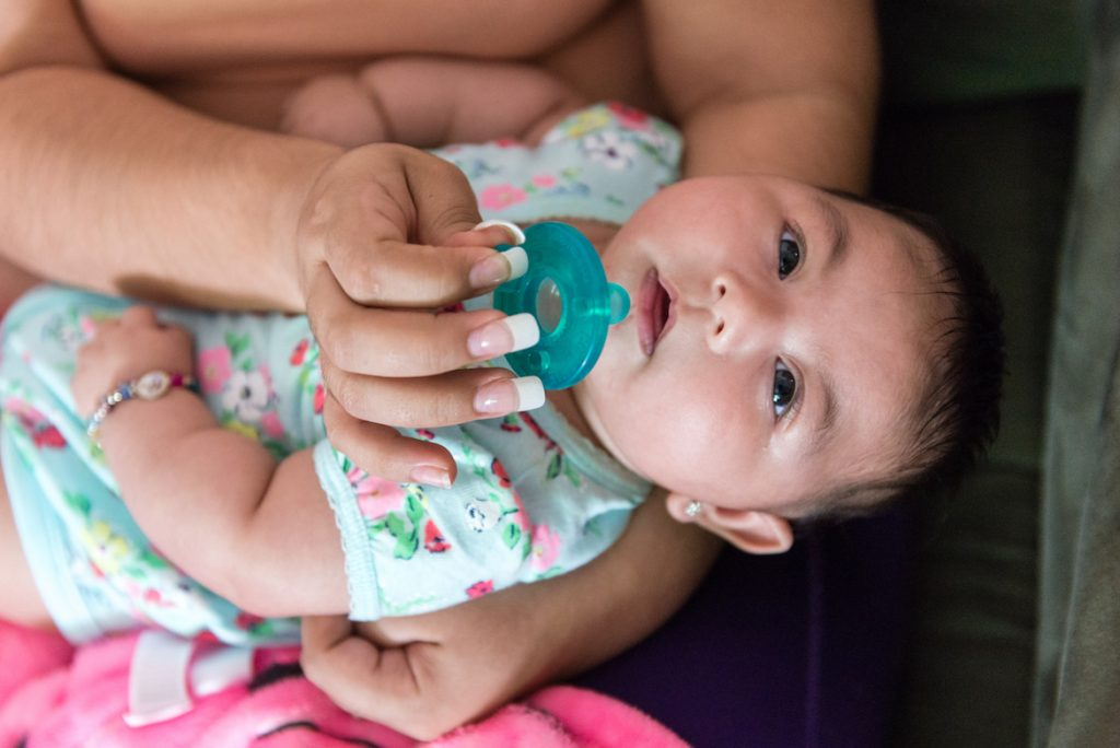 Three-month-old Aryanna Guadalupe Sanchez-Rios rests on her mother's lap on May 3, 2017. Rios was born with Zika-induced microcephaly, a condition in which the head is smaller than average. (Heidi de Marco/KHN)