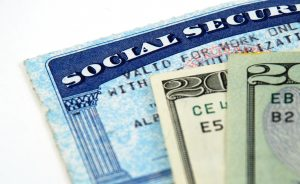 stock pictures of a social security card and money. Photo by Albert Lozano-Nieto/Adobe Stock Images