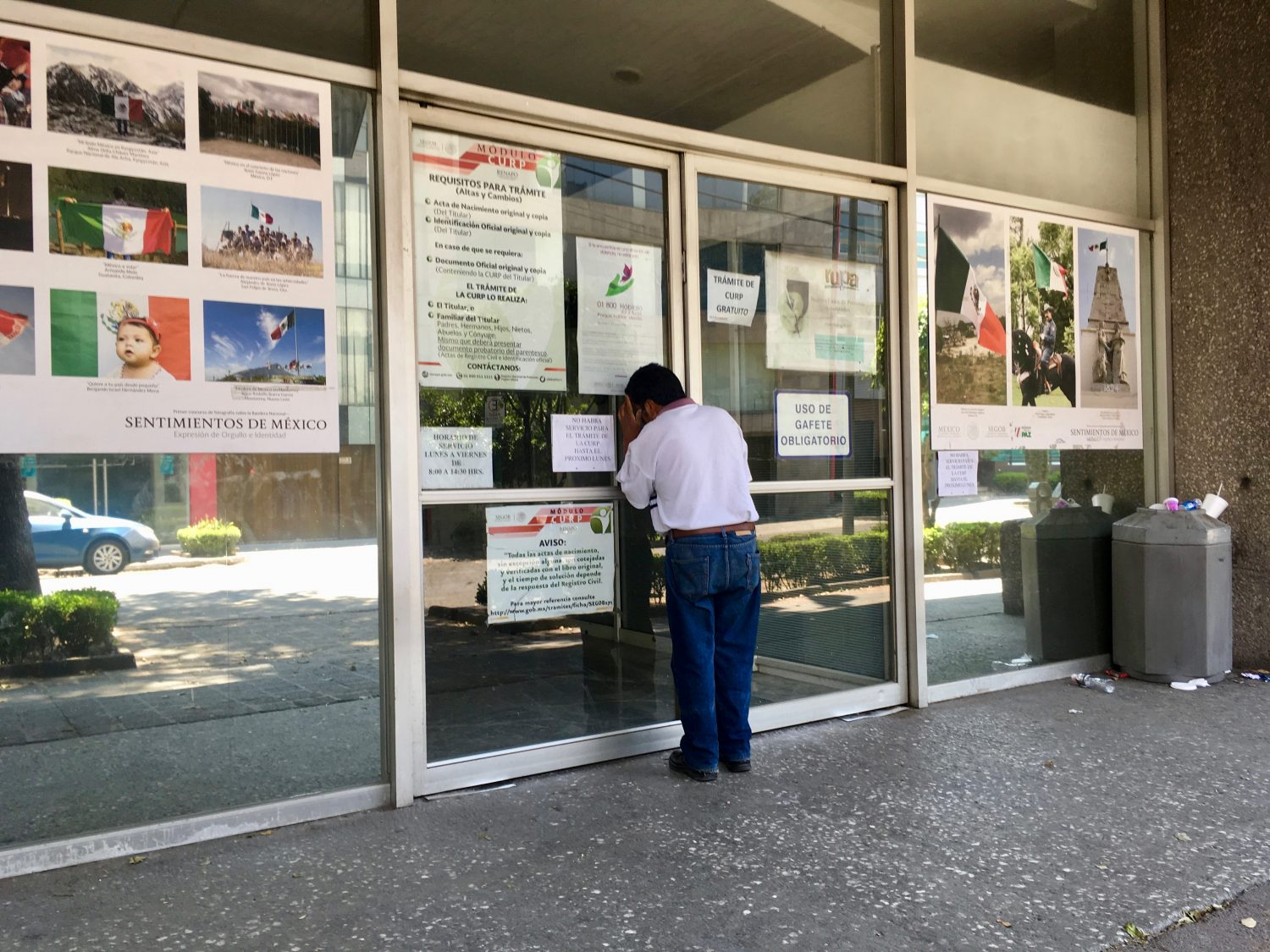 A man stares into the window of the Mexico City building that houses Mexico's Commission for the Aid of Refugees (COMAR). Photo by Hannah Carrese