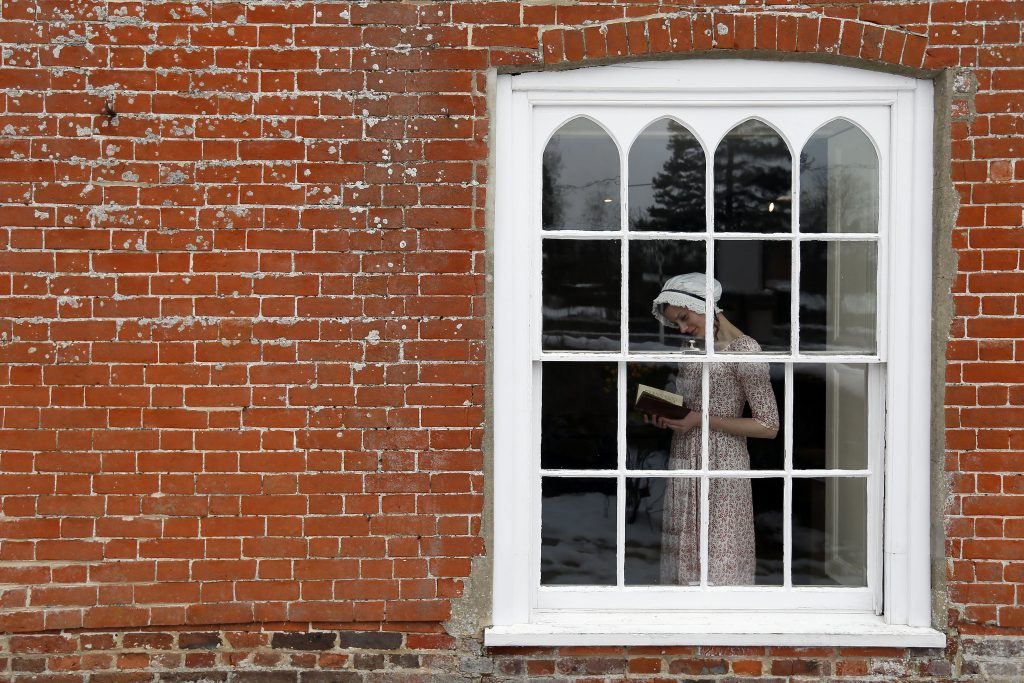 "Jane Austen House employee Isabel Snowden poses for a photograph in a dress that actress Anne Hathaway wore in the film ""Becoming Jane"", as she holds first edition of 'Pride and Prejudice', at the Jane Austen House in Chawton, southern England January 24, 2013. The museum is looking forward to the 200th anniversary of the publication of Austen's novel 'Pride and Prejudice', on Monday. REUTERS/Stefan Wermuth (BRITAIN - Tags: ANNIVERSARY ENTERTAINMENT SOCIETY) - RTR3CWDG"