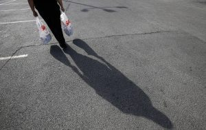 Delores Leonard carries her groceries home after working a shift at a McDonald's Restaurant in Chicago, Illinois, September 25, 2014. Leonard, a single mother raising two daughters, has been working at McDonald's for seven years and has never made more than minimum wage, but gets some assistance with food stamps. Picture taken September 25, 2014. REUTERS/Jim Young (UNITED STATES - Tags: BUSINESS EMPLOYMENT) - RTR4AK8X