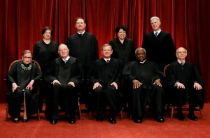 FILE PHOTO: U.S. Chief Justice John Roberts (seated C) leads Justice Ruth Bader Ginsburg (front row, L-R), Justice Anthony Kennedy, Justice Clarence Thomas, Justice Stephen Breyer, Justice Elena Kagan (back row, L-R), Justice Samuel Alito, Justice Sonia Sotomayor, and Associate Justice Neil Gorsuch in taking a new family photo including Gorsuch, their most recent addition, at the Supreme Court building in Washington, D.C., U.S., on June 1, 2017. REUTERS/Jonathan Ernst/File Photo - RTS18I19