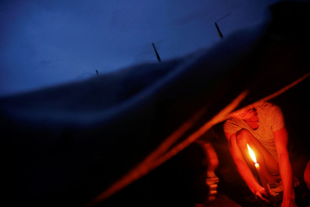 A man lights a candle in his family's shack in an area where, according to local residents, several people have been killed in police operations since the beginning of country's war on drugs, in Manila, Philippines. Photo taken in November 2016. Photo by Damir Sagolj/Reuters