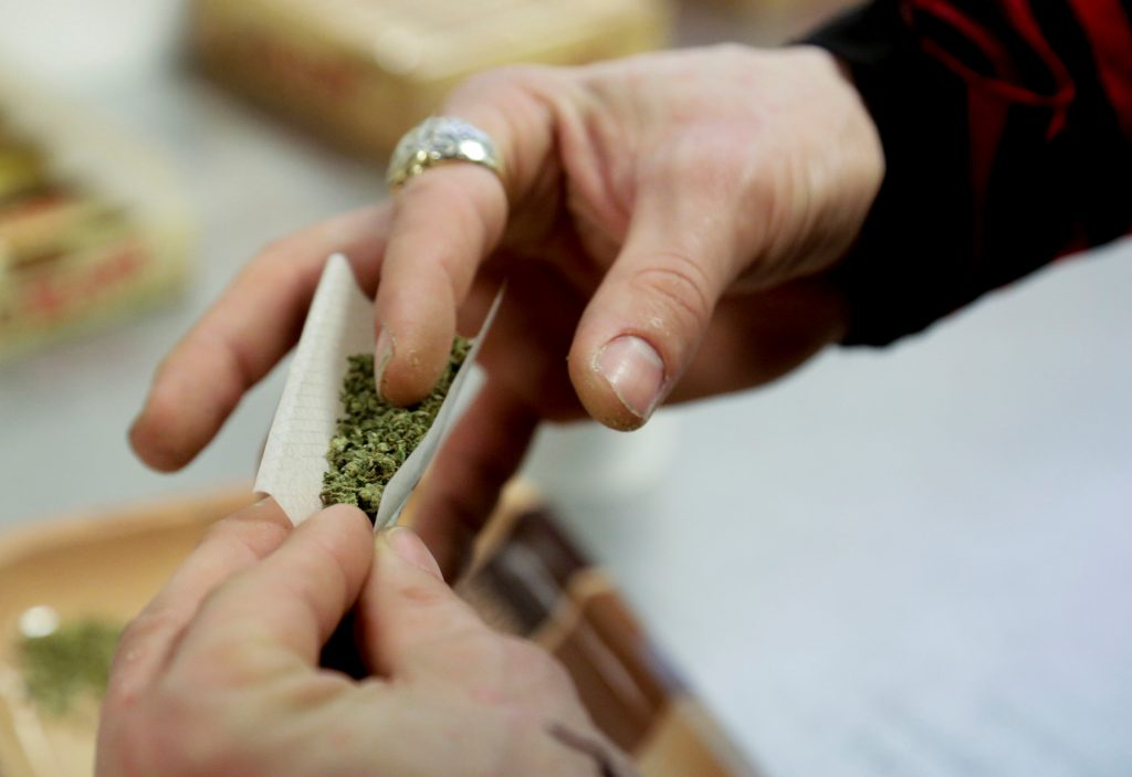 A participant practices rolling a joint