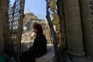 A displaced woman sits near the ruined Grand al-Nuri Mosque in the Old City of Mosul