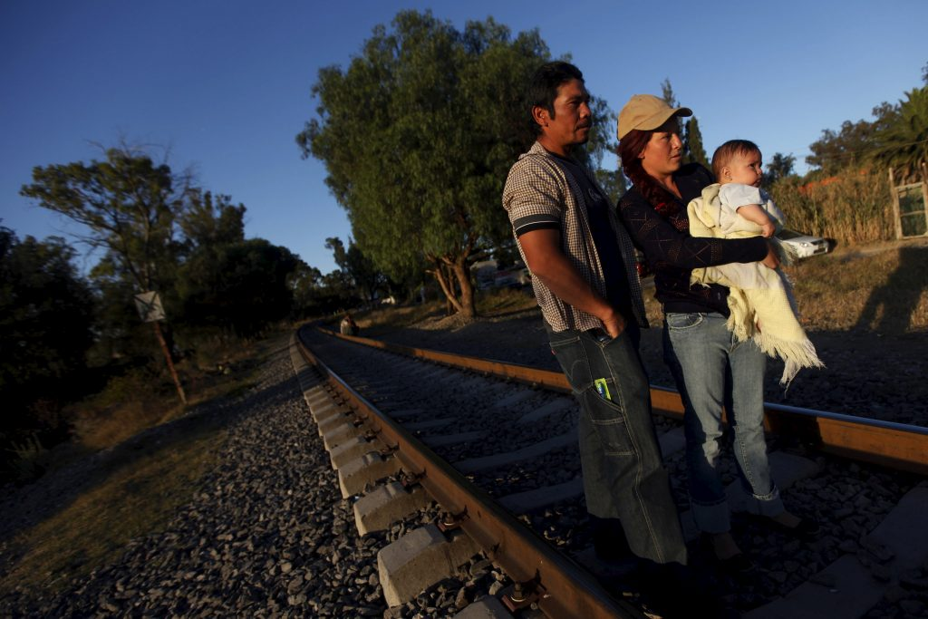 """An illegal Salvadoran migrant couple is seen on railway track with their son Andrew, six months, during the arrival of the """"Caravana de Madres Centroamericanas"""" (Caravan of Central American Mothers) to Huehuetoca October 26, 2012. Picture taken October 26, 2012. REUTERS/Edgard Garrido/Files - RTSDPEN"""