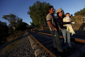 "An illegal Salvadoran migrant couple is seen on railway track with their son Andrew, six months, during the arrival of the ""Caravana de Madres Centroamericanas"" (Caravan of Central American Mothers) to Huehuetoca October 26, 2012. Picture taken October 26, 2012. REUTERS/Edgard Garrido/Files - RTSDPEN"