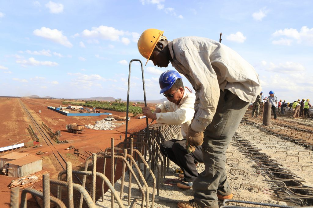 A Chinese engineer and a local construction worker build a section of the Mombasa-Nairobi standard gauge railway in Emali, Kenya on Oct. 10, 2015. Photo by Noor Khamis/Reuters