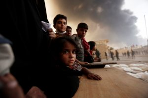 Newly displaced people wait to receive food supplies at a processing center for displaced people In Qayyara