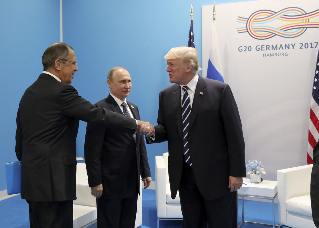 U.S. President Donald Trump (right) shakes hands with Russian Foreign Minister Sergey Lavrov as Russian President Vladimir Putin stands nearby during a meeting on the sidelines of the G20 summit in Hamburg, Germany on July 7. Photo by Sputnik/Mikhail Klimentyev/Kremlin via Reuters