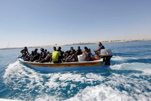 Migrants ride in a boat after they were rescued by Libyan coastguard off the coast of Gharaboli, east of Tripoli