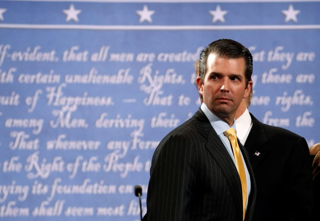 Donald Trump Jr. stands onstage with his father then-presidential nominee Donald Trump after a debate against Democratic n...