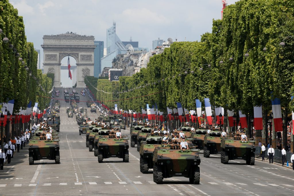 Armored vehicles roll down the banner-lined Champs-Elysee avenue. Photo by Gonzalo Fuentes/Reuters