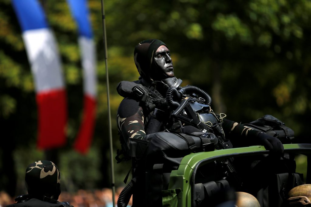 A camouflaged special forces member takes part in the parade. Photo by Stephane Mahe/Reuters