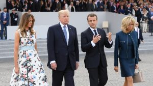 French President Emmanuel Macron and his wife Brigitte Macron walk with US President Donald Trump and US First Lady Melania Trump during the traditional Bastille Day military parade in Paris