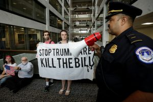 Healthcare activists get a police warning during a protest to stop the Republican health care bill at Hart Senate Office Building in Washington, D.C., in July. Photo by Yuri Gripas/Reuters