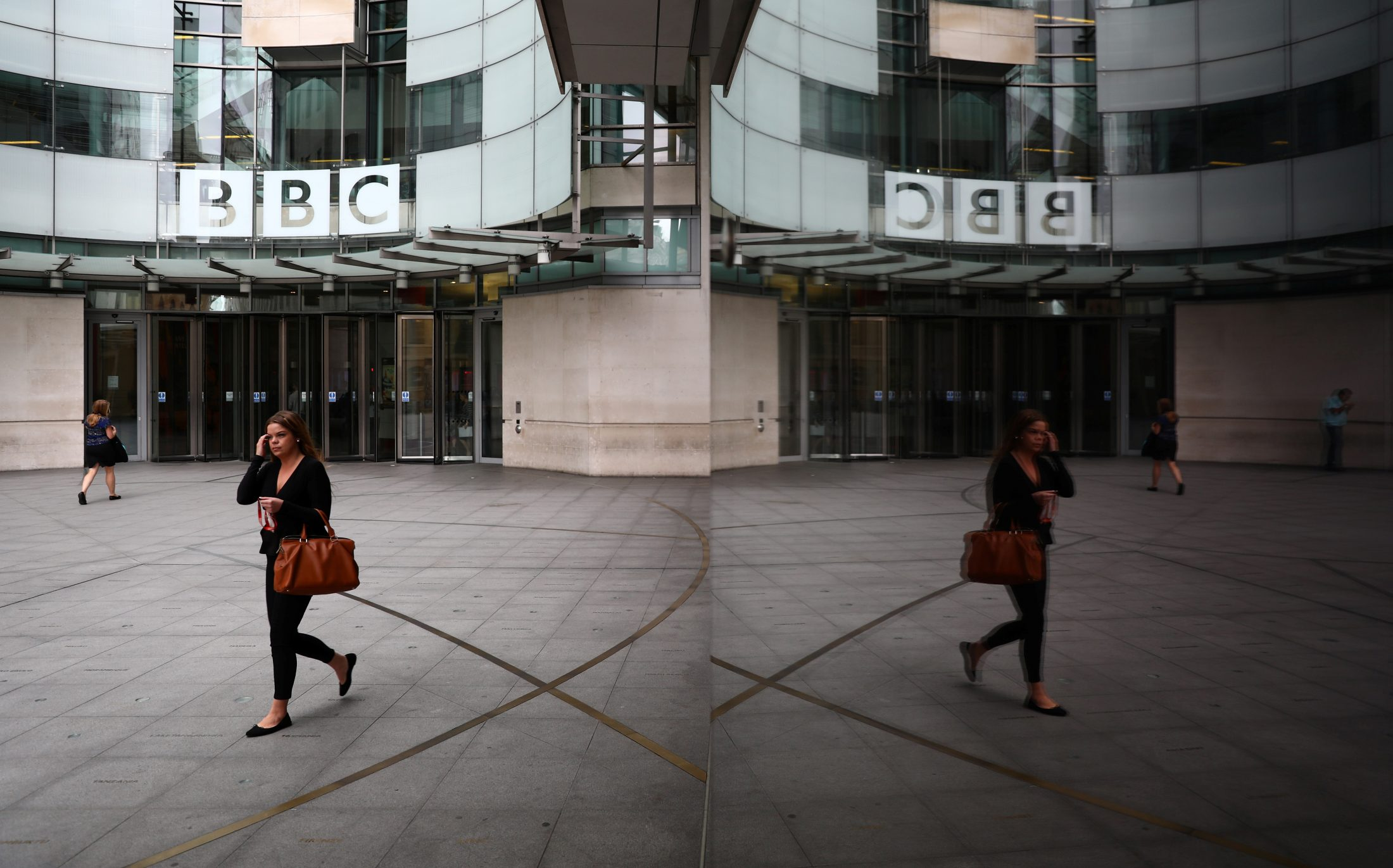 A woman is reflected as she passes the BBC's Broadcasting House in London, Britain. Photo by Neil Hall/Reuters