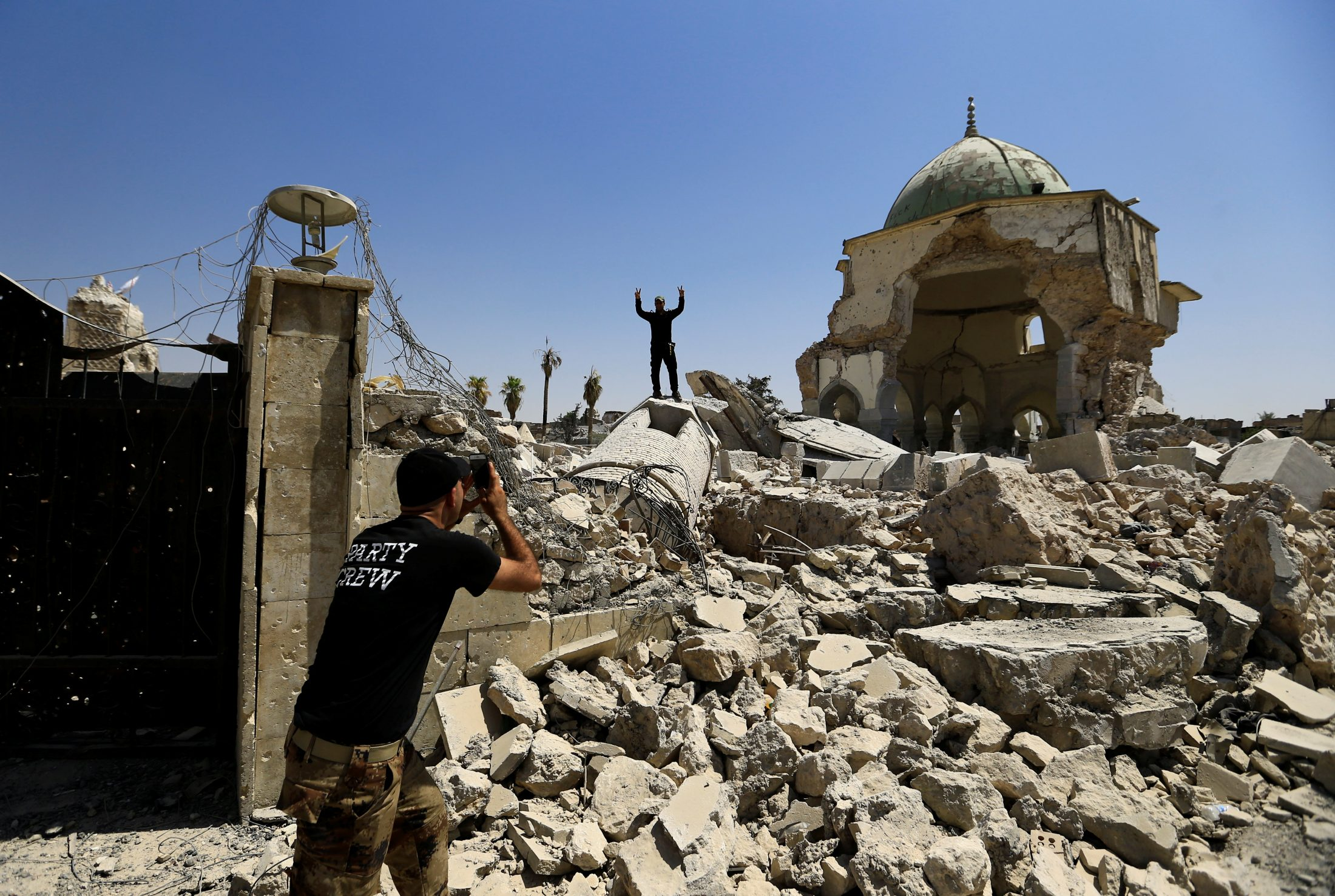 Members of the Counter Terrorism Service (CTS) take a selfie in front of the ruins of Grand al-Nuri Mosque in the Old City of Mosul,Iraq. Photo by Thaier Al-Sudani/Reuters