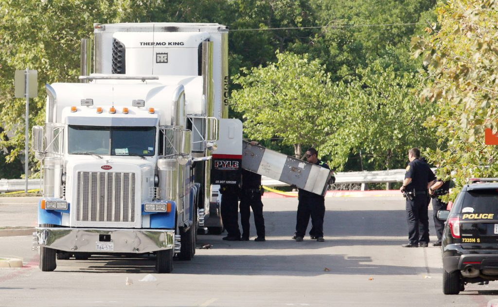 Police officers work on a crime scene after 10 undocumented immigrants being smuggled into the U.S. were found dead inside a sweltering 18-wheeler trailer parked behind a Walmart store in San Antonio. Photo by Ray Whitehouse/Reuters
