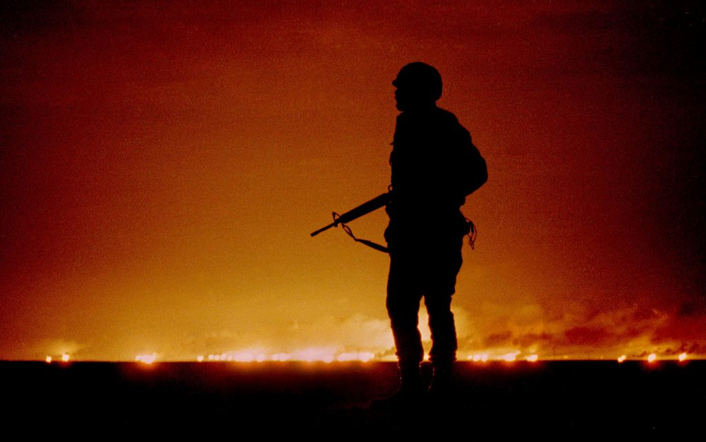 A file photo dated February 26, 1991 of a U.S. soldier standing night guard as oil wells burn in the distance in Kuwait, just south of the Iraqi border on the last night of the Gulf War. Photo by Reuters