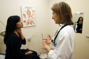 Discovery Communications Wellness Center Medical Director Dr. Liz Sequeira discusses symptoms with patient Bonnary Lek (L) at the clinic in the Discovery headquarters in Silver Spring, Maryland December 3, 2009. Sequeira says seeing patients in her office at Discovery Communications Inc's modern headquarters is like stepping back in time and being an old-time small town doctor. As Democratic lawmakers in Washington inch ahead with plans to overhaul the U.S. healthcare system, companies like Discovery are striking out on their own -- whether through on-site doctors or diet plans -- to rein in soaring costs in a nation where employers still pay for the bulk of medical care. Picture taken December 3, 2009. To match Special Report USA-HEALTHCARE/WELLNESS REUTERS/Jim Bourg (UNITED STATES HEALTH BUSINESS SOCIETY) - RTXRMUU