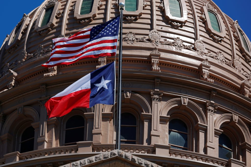 The U.S flag and the Texas State flag fly over the Texas State Capitol as the state senate debates the #SB6 bathroom bill in Austin
