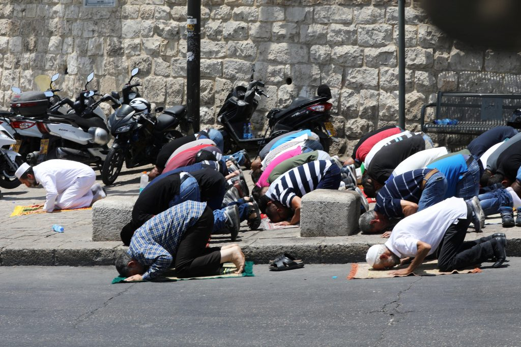 Palestinians pray just outside Jerusalem's Old City in protest over Israel's new security measures at the entrance to the compound known to Muslims as Noble Sanctuary and to Jews as Temple Mount in Jerusalem's Old City