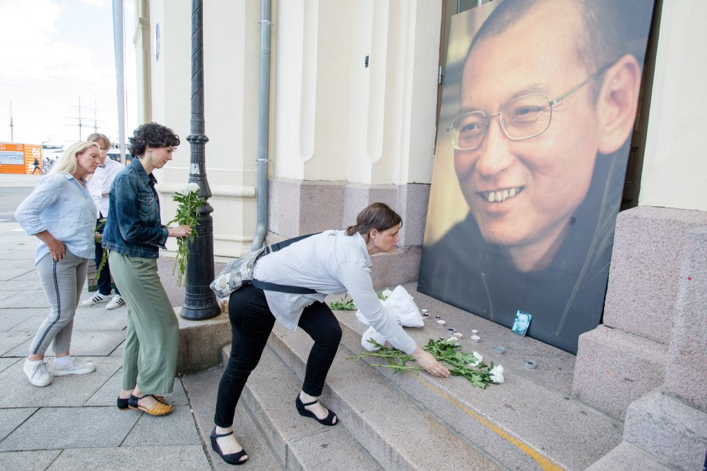 People place flowers and light candles in front a picture of late Nobel Peace Laureate Liu Xiaobo outside the Nobel Peace Center in Oslo, Norway July 13, 2017. NTB Scanpix/Audun Braastad via REUTERS ATTENTION EDITORS - THIS IMAGE WAS PROVIDED BY A THIRD PARTY. NORWAY OUT. NO COMMERCIAL OR EDITORIAL SALES IN NORWAY. TPX IMAGES OF THE DAY - RTX3BC7X