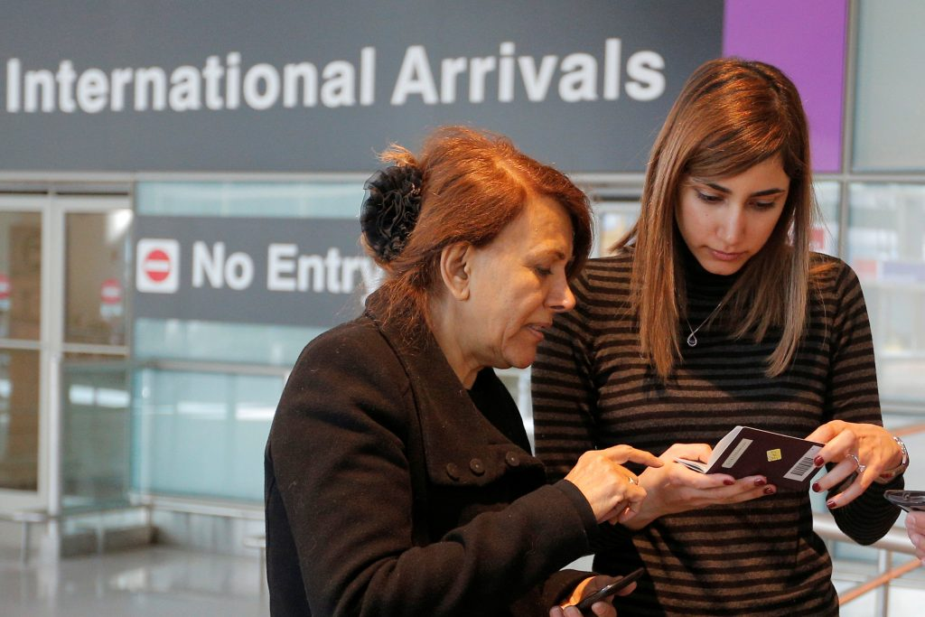 Negar Jourabchian looks at her mother Niloufar's passport, after she traveled to the U.S. from Iran following a federal court's temporary stay of U.S. President Donald Trump's executive order travel ban, at Logan Airport in Boston, Massachusetts, U.S. February 6, 2017. REUTERS/Brian Snyder - RTX2ZWEY