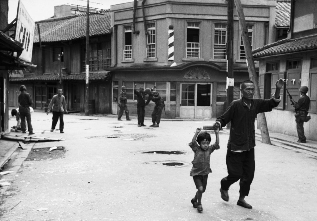 US soldiers stop and search residents of a South Korean city, looking for suspected Communist sympathizers. A man and young boy walk down the street with their hands in the air. (Photo by © Hulton-Deutsch Collection/CORBIS/Corbis via Getty Images)