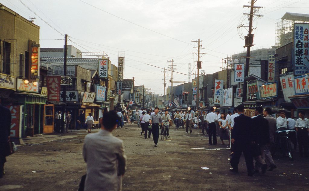 View of a bustling street scene during the Korean War, with multiple store signs, power lines, and villagers walking and bicycling , Taejin, South Korea, 1952. (Photo by Smith Collection/Gado/Getty Images)