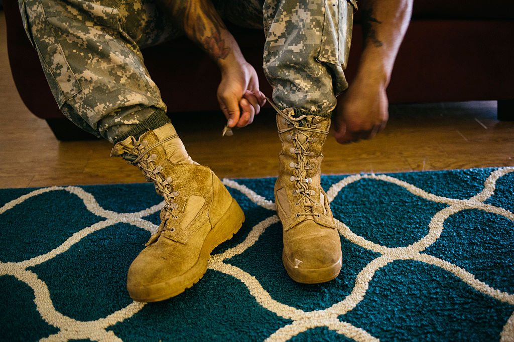 Army Sergeant Shane Ortega laces up boots before posing for a portrait at home at Wheeler Army Airfield on March 26, 2015 in Wahiawa, Hawaii.  (Photo by Kent Nishimura/For The Washington Post via Getty Images)