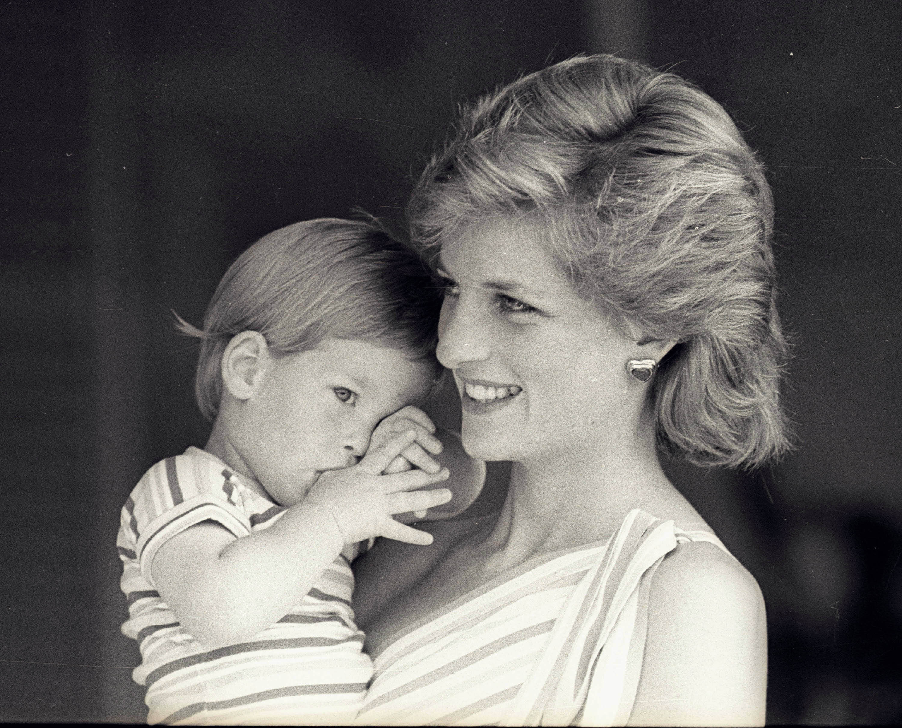 Prince Harry tries to hide behind his mother Princess Diana at Marivent Palace in Spain on Aug. 9, 1988. The family was visiting King Juan Carlos and Queen Sofia. Photo by Hugh Peralta/Reuters