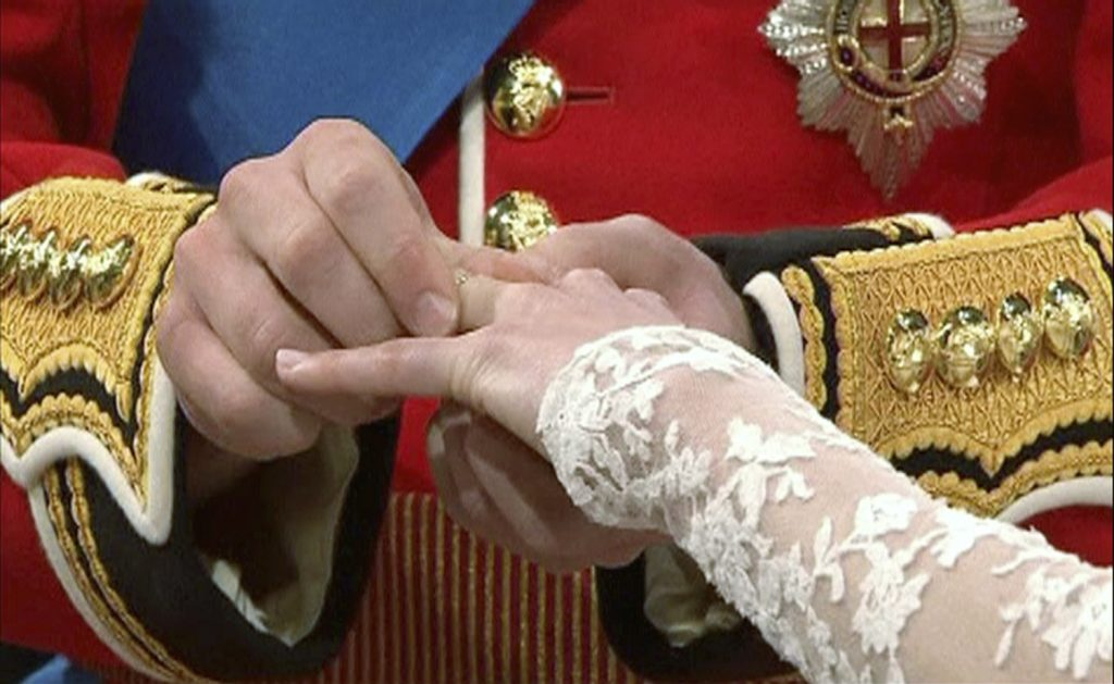 Prince William puts a ring on Catherine Middleton's hand during their wedding at Westminster Abbey in London. Pool photo via Reuters