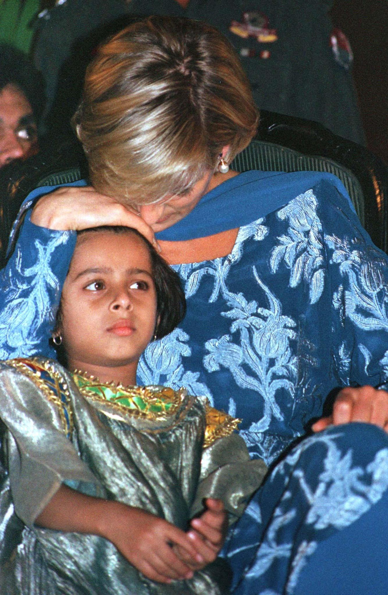 Princess Diana comforts 5-year-old Iqra Asif, sister of a cancer patient Khurram Zia, 14, at a hospital in Lahore on May 23, 1997. Photo by Muzammil Pasha/Reuters