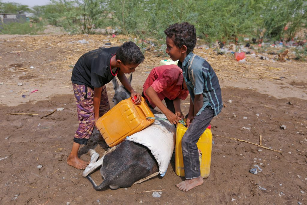 Boys load jerry cans of drinking water onto a donkey in Bajil in western Yemen. Photo by Abduljabbar Zeyad/Reuters