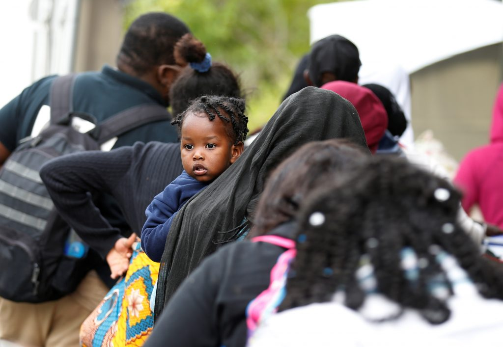 A line of asylum seekers who identified themselves as from Haiti wait to enter into Canada from Roxham Road in Champlain, New York on Aug. 7. Photo by Christinne Muschi/Reuters