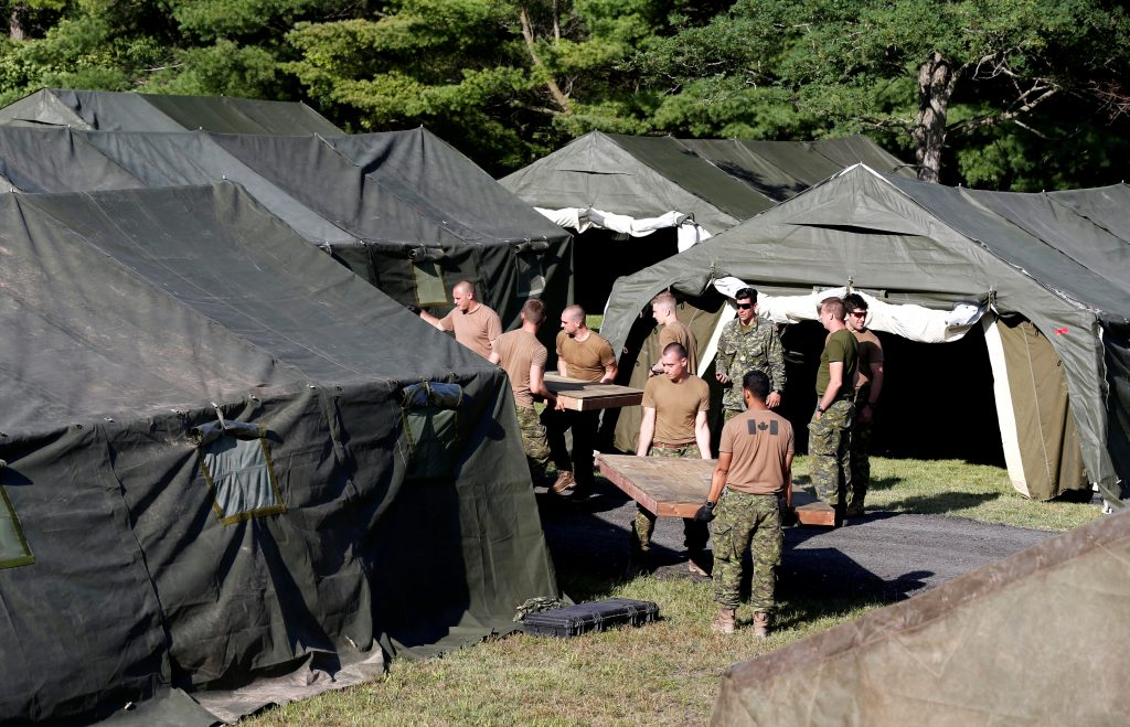 Members of the Canadian Armed Forces carry wooden flooring into the tents they set up for asylum seekers. Photo by Christinne Muschi/Reuters