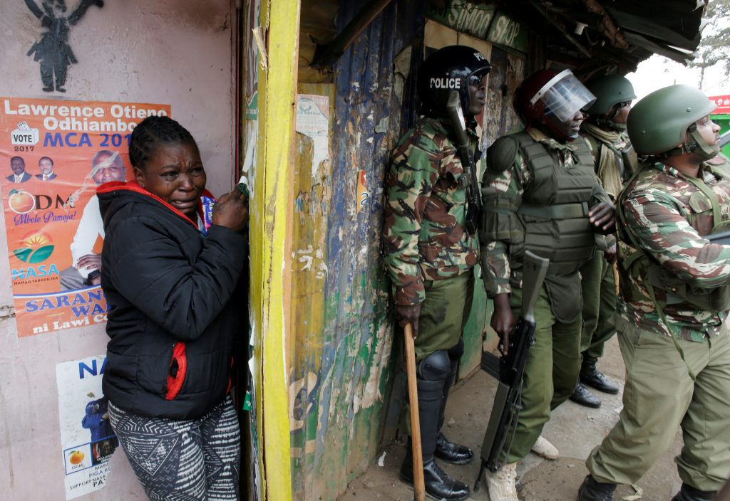 A woman cries as she stand behind policemen during clashes between supporter of opposition leader Raila Odinga and policemen in Kibera slum in Nairobi, Kenya, August 12, 2017. Photo by Goran Tomasevic/ Reuters