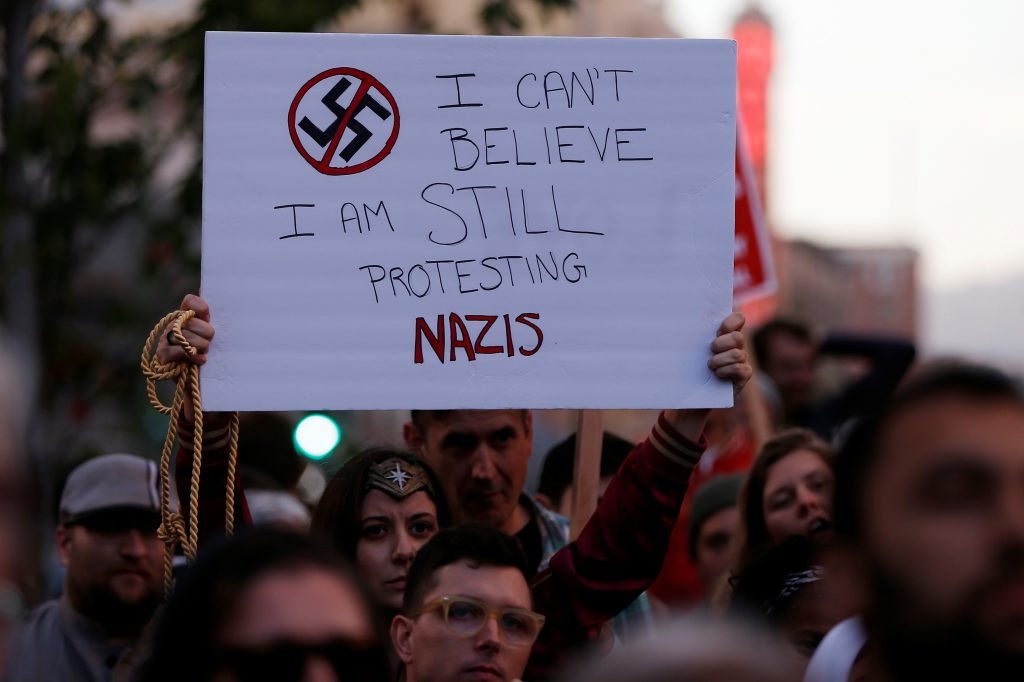 Demonstrator holds signs during a rally in response to the Charlottesville, Virginia car attack in Oakland