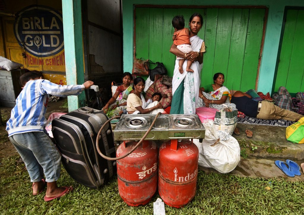 Flood-affected families take shelter in front of a shop in the Jakhalabandha area of Nagaon district in Assam, India. Photo by Anuwar Hazarika/Reuters