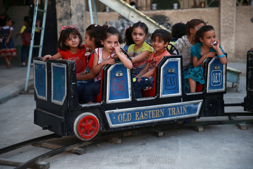 Students ride a miniature train at a school in Douma, near Damascus. About half of the Syrian population is either displaced within the country or in other countries. Photo by Bassam Khabieh/Reuters